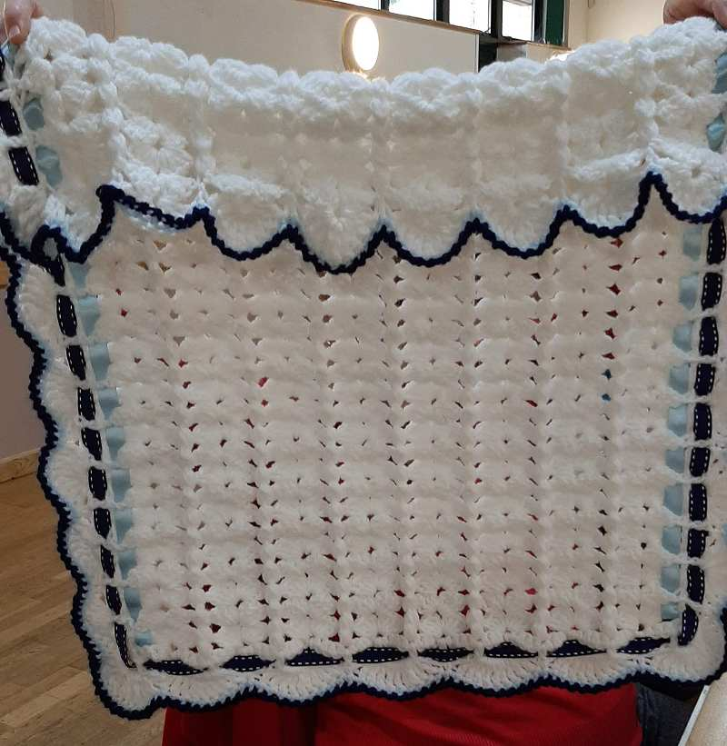 A baby blanket crocheted by Ann Rice.