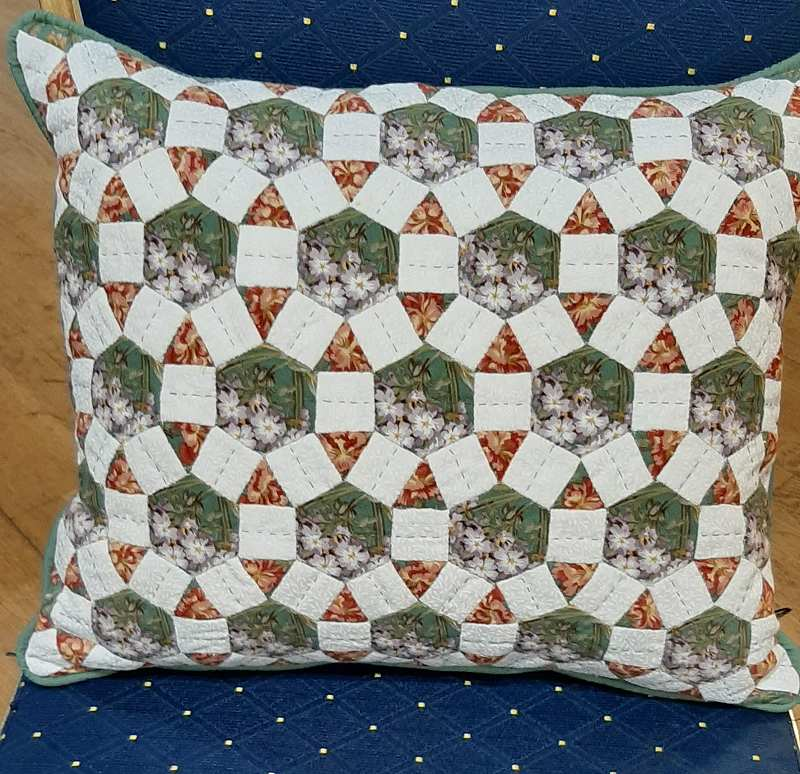 A cushion made with Wellington Hexagons by Penny.
