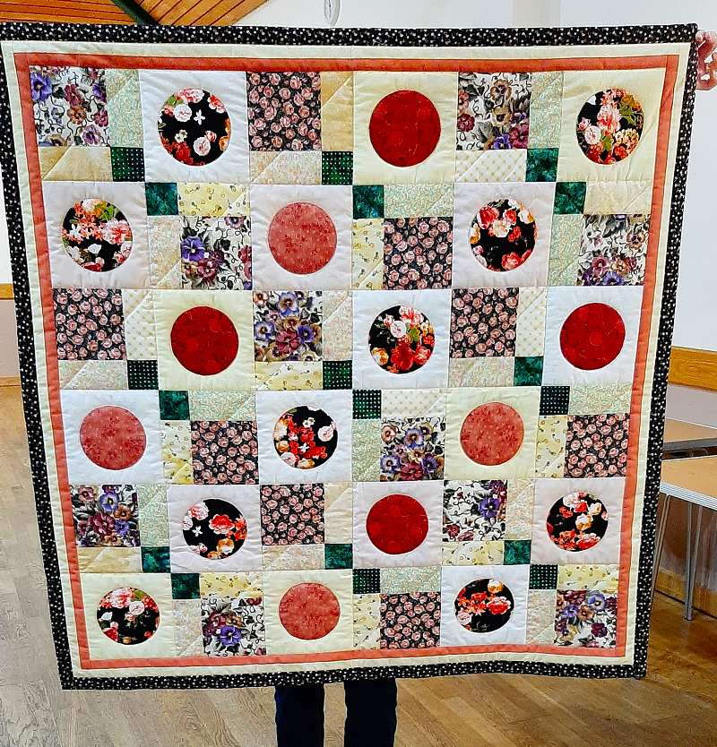 Margaret Morris has gone big this time making this quilt using fabric scraps including a piece of her school dress.